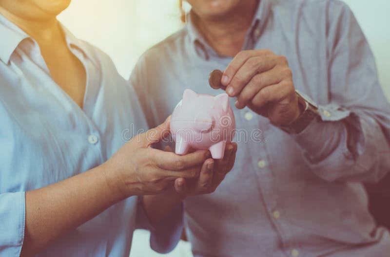 Hogere paarhanden die muntstuk samenbrengen aan spaarvarken voor pensionering die, geldconcept bewaren stock foto's