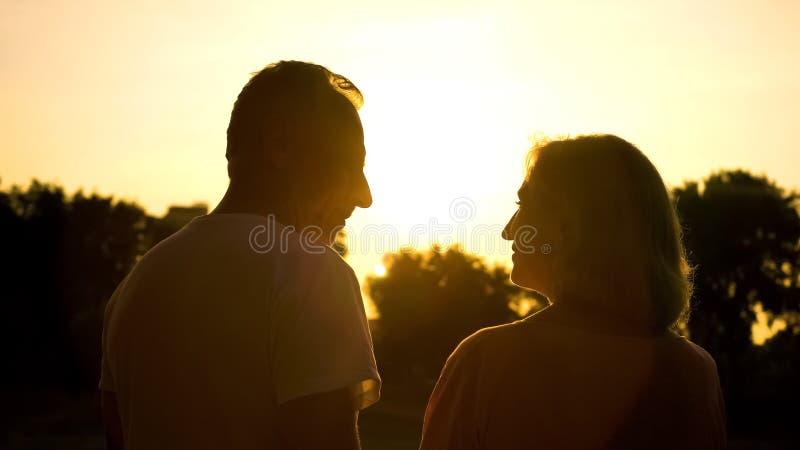 Hogere paarsilhouet het letten op zonsondergang samen, romantische datum in platteland royalty-vrije stock afbeeldingen