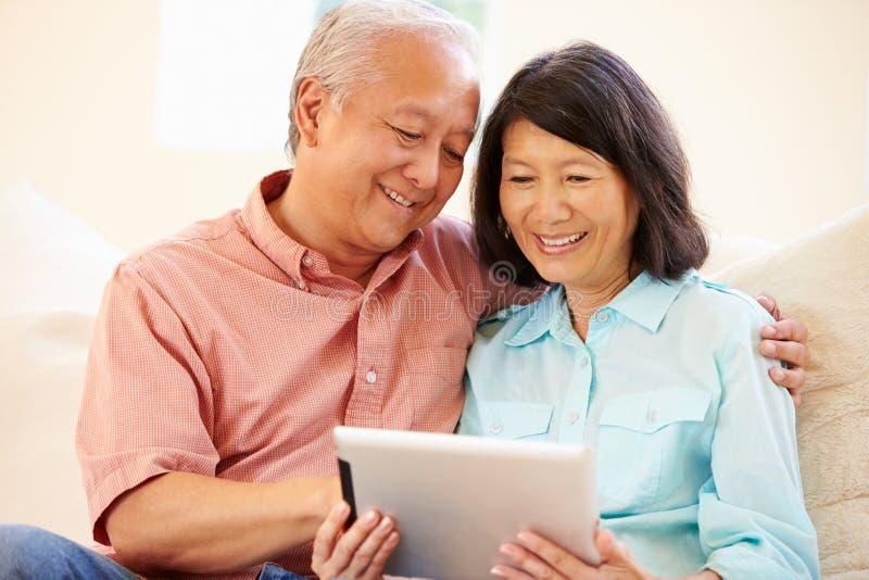 Hogere Paarzitting op Sofa Using Digital Tablet stock afbeeldingen