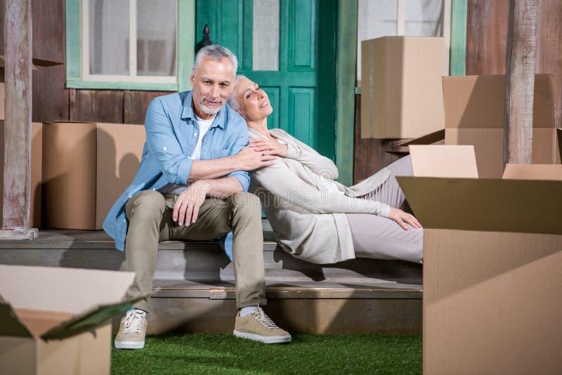 Hogere paarzitting samen op treden van nieuw huis, verhuizingsconcept royalty-vrije stock fotografie