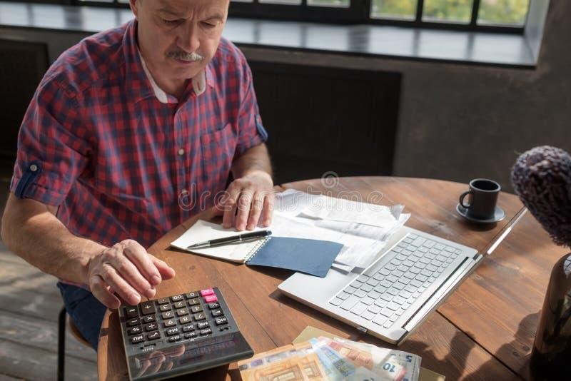 Hogere paniekzaaierij die bezig is met berekening, waarbij geld en rekeningen thuis worden geteld royalty-vrije stock afbeelding