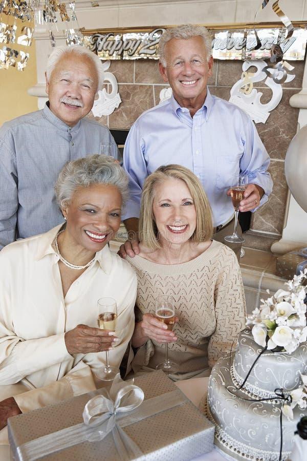 Hogere Paren met Champagne In Party stock foto