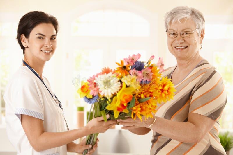 Hogere patiënt die bloemen geeft aan verpleegster royalty-vrije stock afbeelding