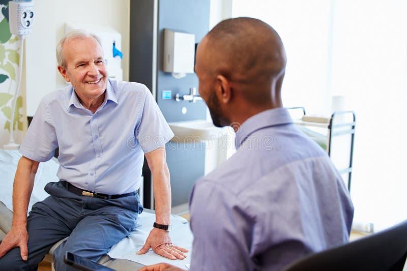 Hogere Patiënt en Artsen het Ziekenhuiszaal van Have Consultation In stock foto