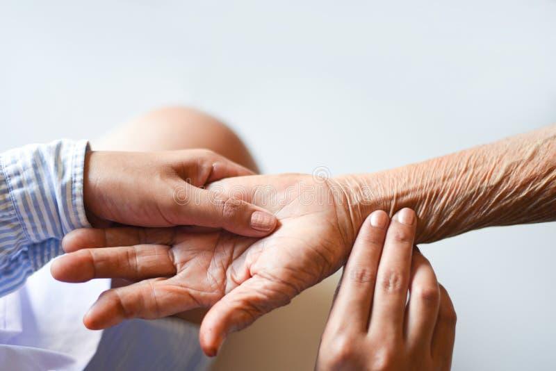 Hogere patiënt en verpleegster - de Impulsmeting controleert met de hand het hart geduldige hand voor een radiale impuls door vin stock foto's