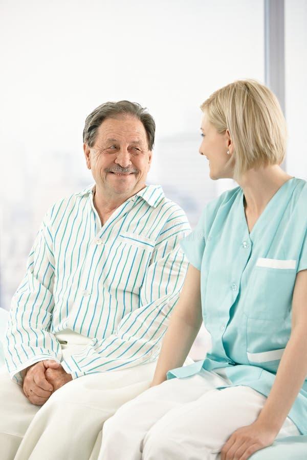 Hogere patiënt in het ziekenhuis met verpleegster royalty-vrije stock afbeelding