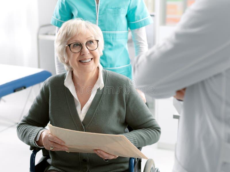 Hogere patiënt op rolstoel met medisch personeel royalty-vrije stock foto's