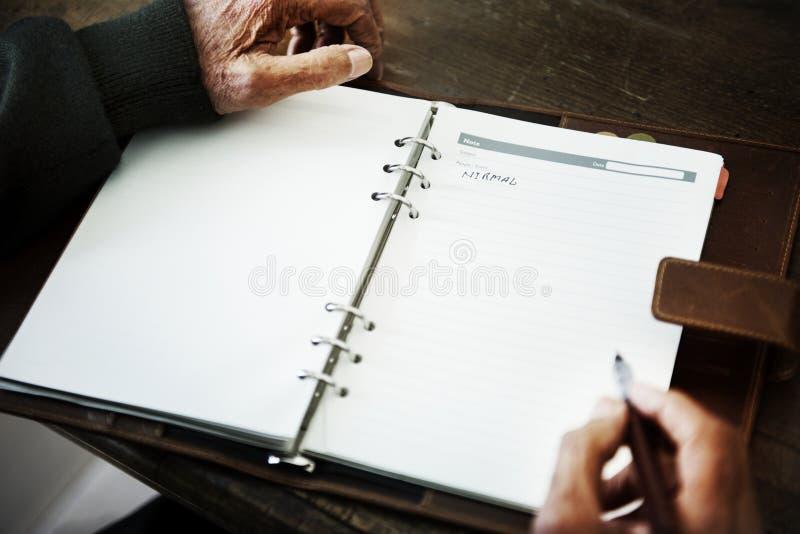 Hogere persoons` s hand die een dagboek schrijven royalty-vrije stock foto's