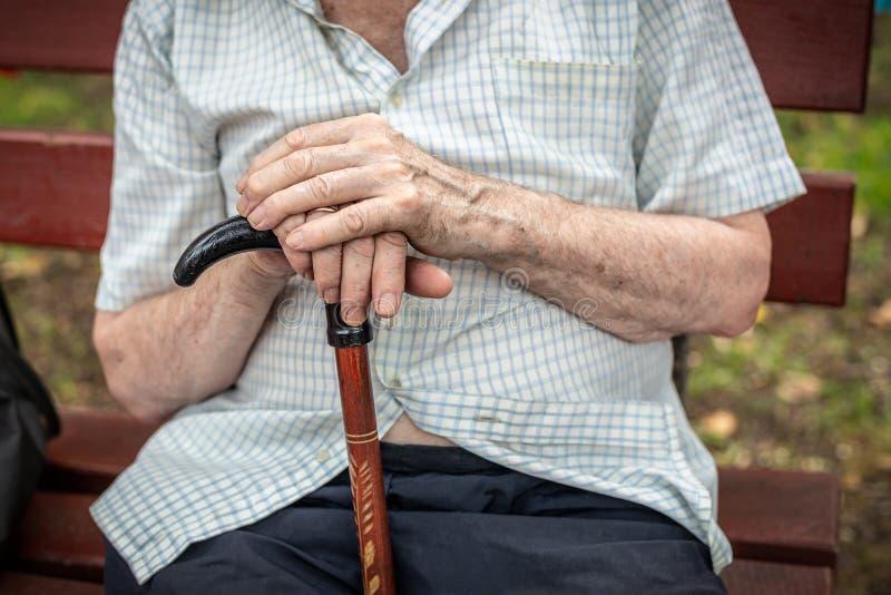 Hogere persoonszitting op houten bank in openlucht Oude mensenhanden die wandelstok houden Armoede, eenzaamheid en stock foto's