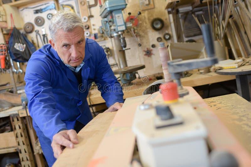 Hogere restaurateur die met antiek decorelement werken in workshop royalty-vrije stock foto
