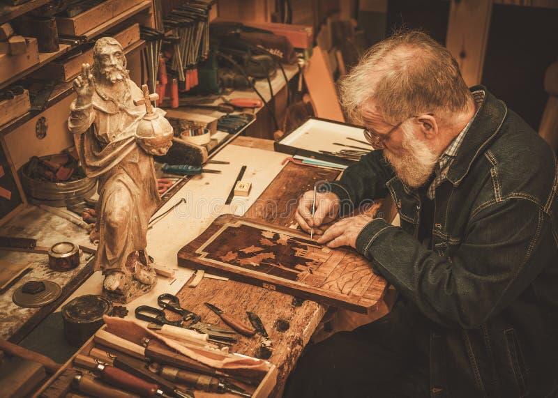 Hogere restaurateur die met antiek decorelement werken in zijn workshop royalty-vrije stock foto