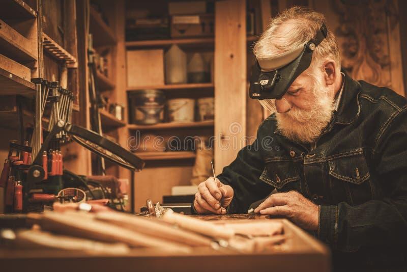 Hogere restaurateur die met antiek decorelement werken in zijn workshop stock afbeelding
