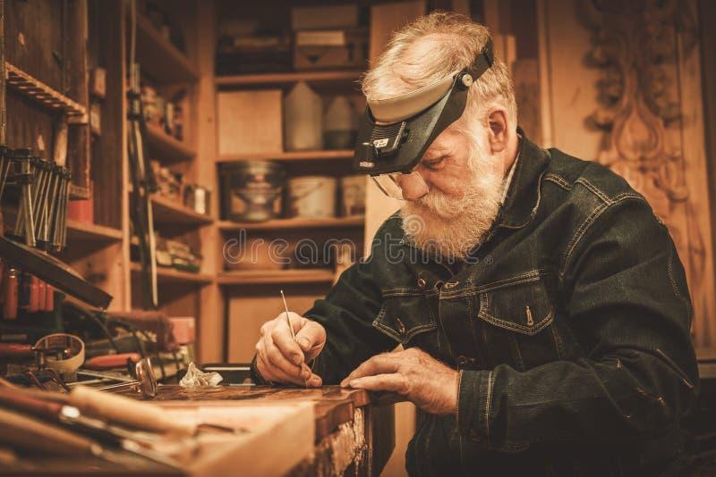 Hogere restaurateur die met antiek decorelement werken in zijn workshop stock fotografie