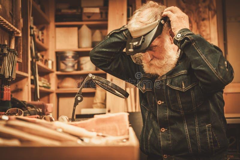 Hogere restaurateur die met antiek decorelement werken in zijn workshop royalty-vrije stock afbeeldingen