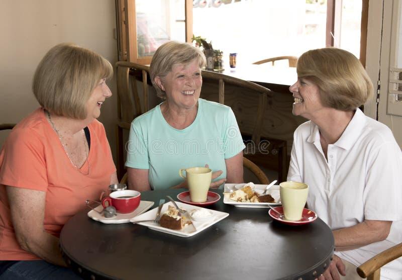Hogere rijpe de vrouwenmeisjes die van de trio mooie middenleeftijd voor koffie en thee met cakes bij koffiewinkel samenkomen die stock afbeelding