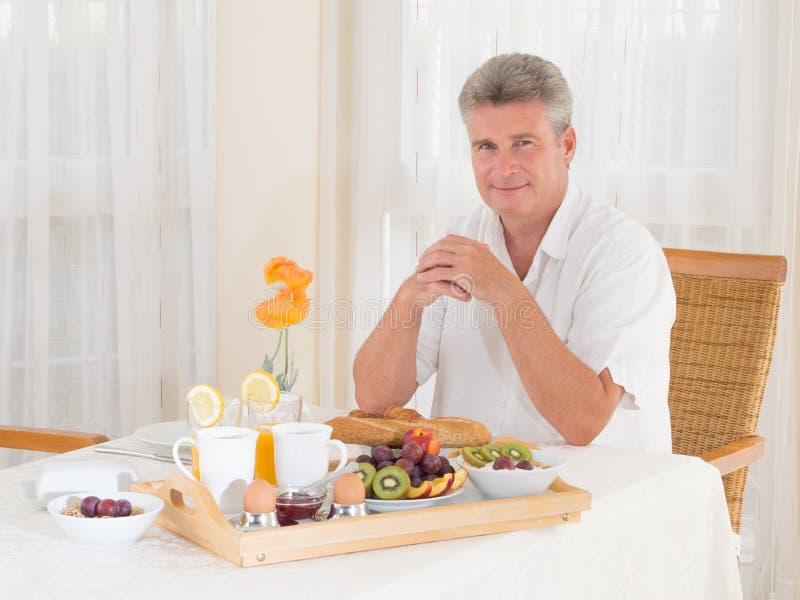 Hogere rijpe mensenzitting neer aan een gezond ontbijt die camera bekijken royalty-vrije stock foto's