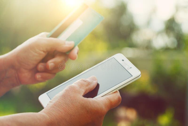 Hogere smartphone van de vrouwenholding en creditcard stock fotografie