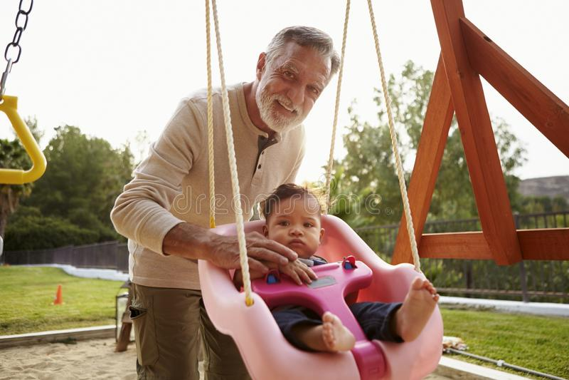 Hogere Spaanse grootvader die zijn babykleinzoon op een schommeling duwen bij een speelplaats in het park royalty-vrije stock foto