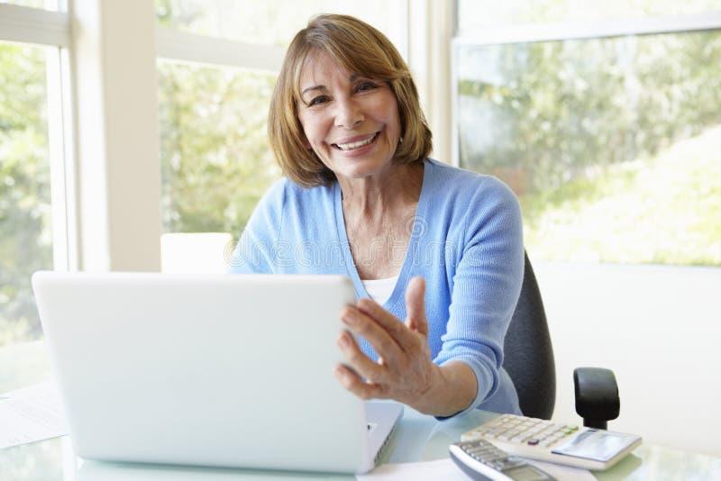 Hogere Spaanse Vrouw die Laptop in Huisbureau met behulp van royalty-vrije stock afbeelding