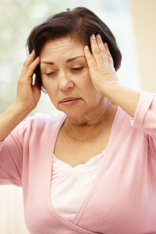Hogere Spaanse vrouw met hoofdpijn stock afbeeldingen