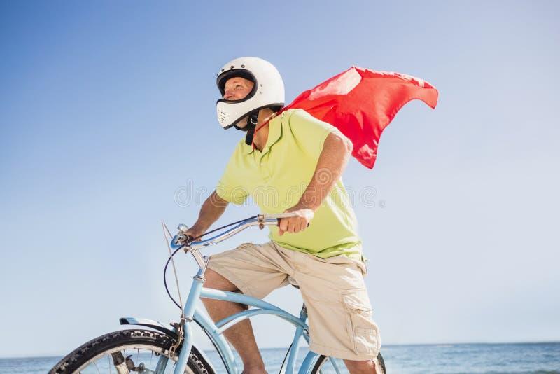 Hogere superhero berijdende fiets stock foto's