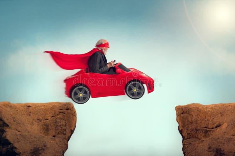 Hogere superhero die een auto drijven van een ravijn royalty-vrije stock foto