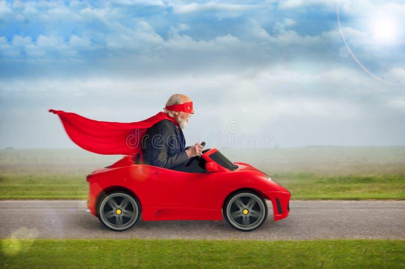 Hogere superhero die een stuk speelgoed sportwagen drijven royalty-vrije stock afbeeldingen