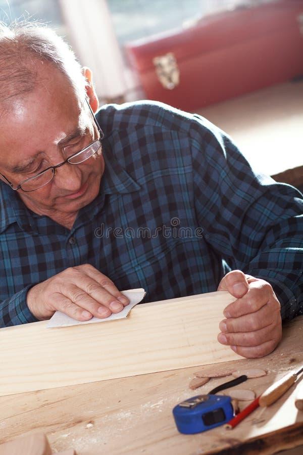 Hogere timmerman die stuk van hout met schuurpapier verzenden stock foto