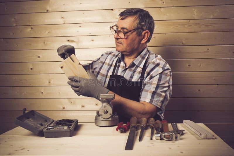 Hogere timmerman die in zijn workshop werken royalty-vrije stock afbeelding