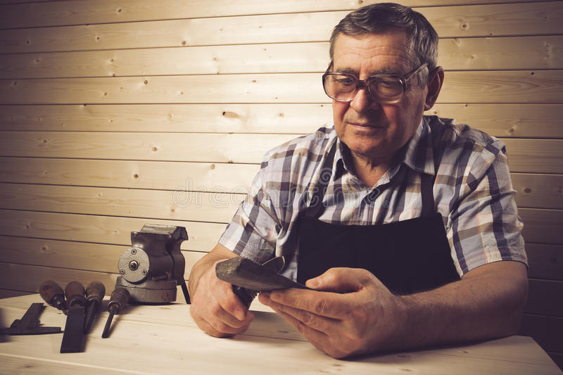 Hogere timmerman die in zijn workshop werken royalty-vrije stock afbeeldingen