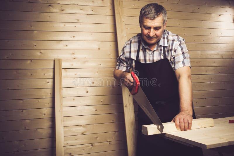 Hogere timmerman die in zijn workshop werken stock foto