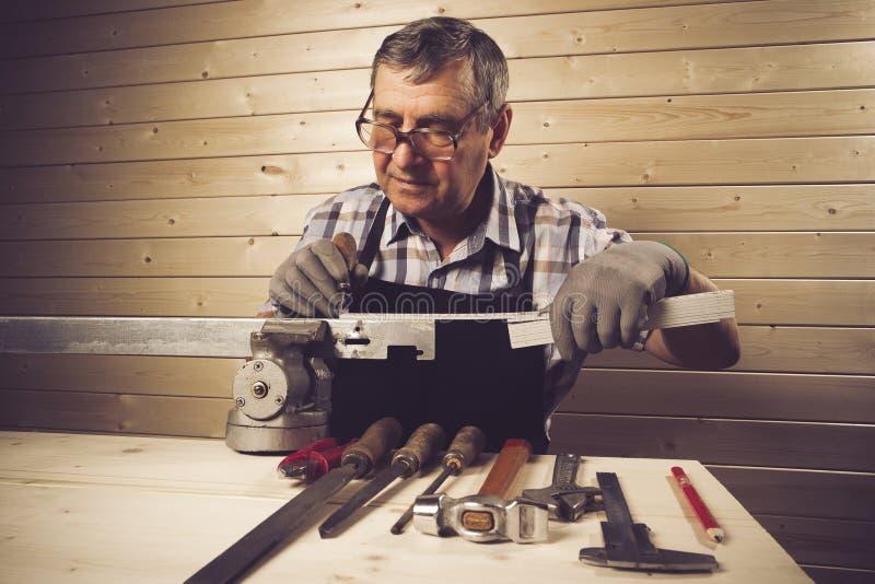 Hogere timmerman die in zijn workshop werken stock fotografie