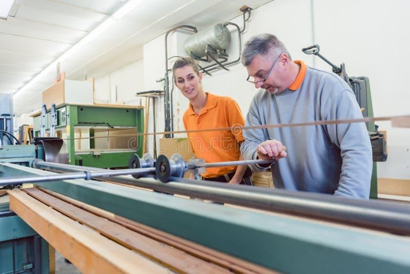Hogere timmerman en vrouwelijke leerling die aan bandmolen werken stock afbeeldingen