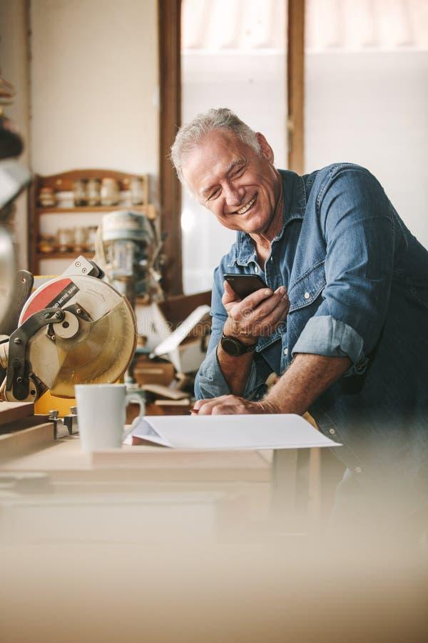 Hogere timmerman op zijn workshop die mobiele telefoon met behulp van stock foto