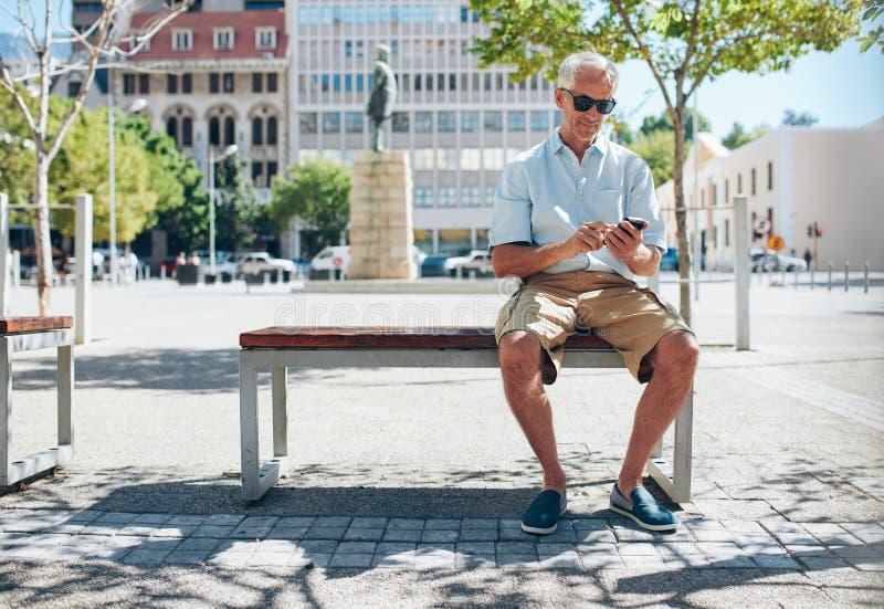 Hogere toerist in de stad die mobiele telefoon met behulp van stock foto's