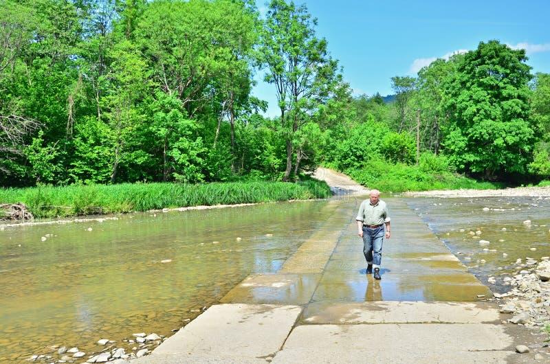 Hogere toerist het doorwaden bergrivier stock foto