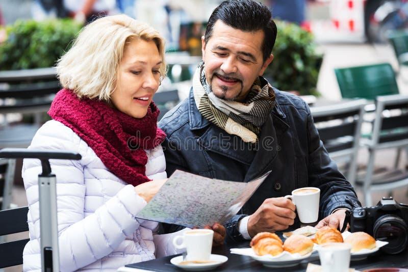 Hogere toeristen die kaart lezen bij koffie stock afbeelding