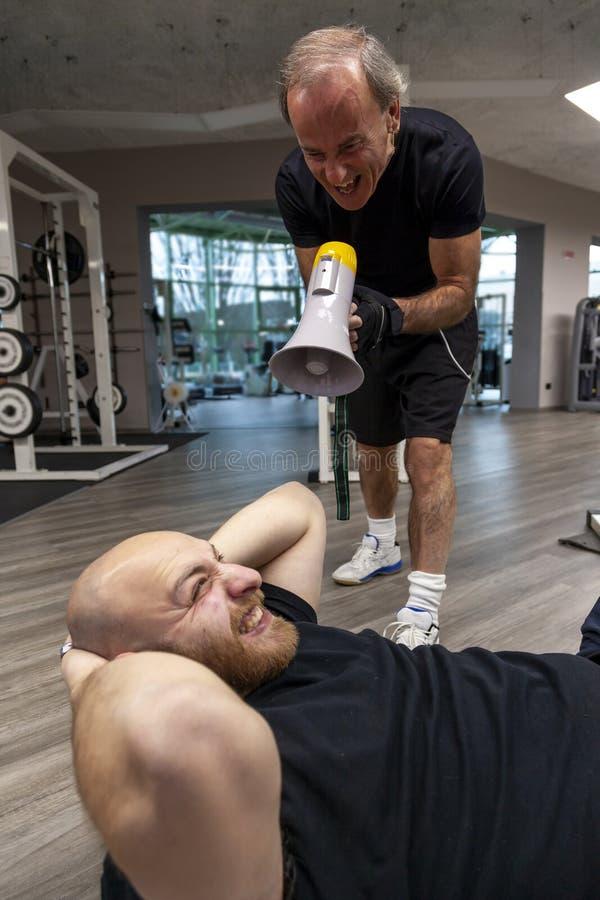 Hogere trainer die met een megafoon bij de jonge atleet gillen stock foto's