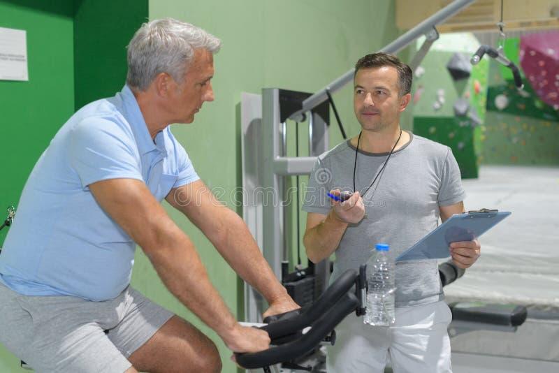 Hogere trein met persoonlijke trainer bij gymnastiek royalty-vrije stock fotografie