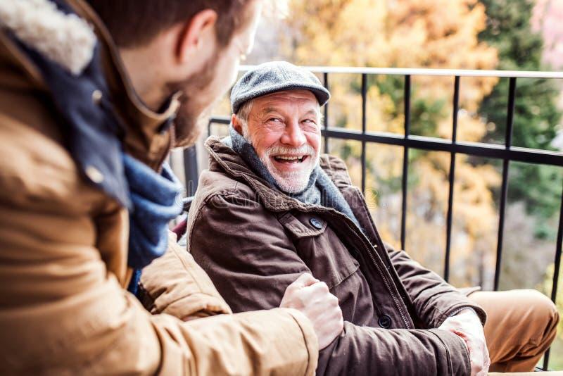Hogere vader in rolstoel en jonge zoon op een gang royalty-vrije stock afbeeldingen