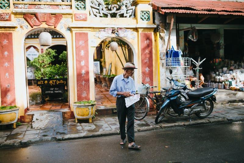 hogere Vietnamese mens die met krant op straat in Hoi An, Vietnam lopen stock foto's