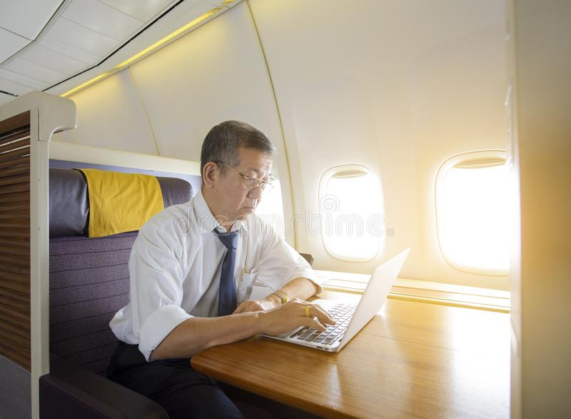 Hogere volwassen Aziatische mens die laptop op luxevliegtuig met behulp van stock afbeelding