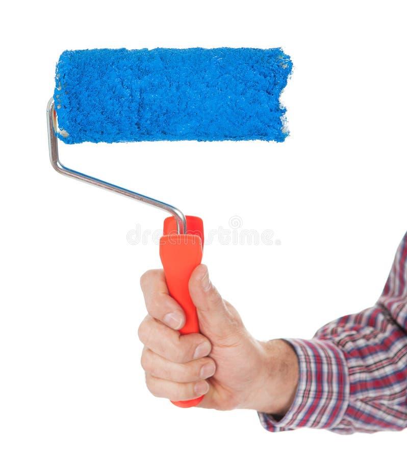 Hogere volwassen het schilderen muur in blauw stock afbeelding