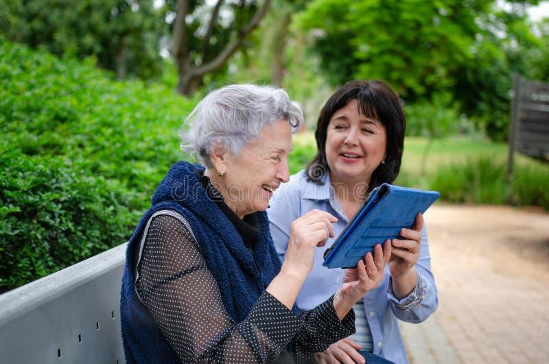 Hogere volwassen vrouw die aan tablet met vrijwilligershulp worden geïntroduceerd royalty-vrije stock fotografie