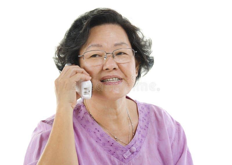 Hogere volwassen vrouw die op telefoon spreken stock fotografie