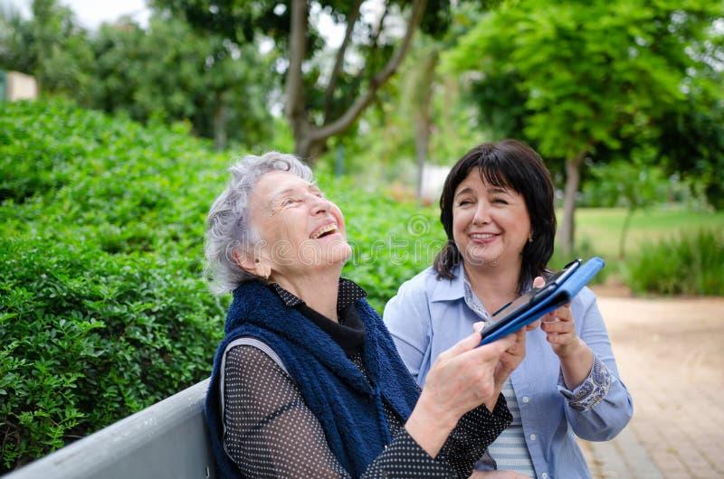 Hogere volwassen vrouw en een werker uit de hulpverleninglach die een tablet in hun handen houden terwijl het zitten op een parkb royalty-vrije stock fotografie