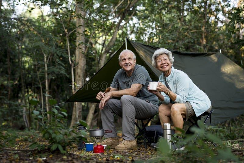 Hogere vrienden die koffie hebben bij een kampeerterrein stock fotografie