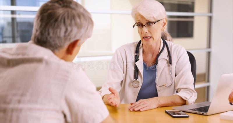 Hogere vrouw arts die aan bejaarde patiënt in het bureau spreken stock foto's