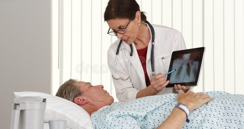 Hogere vrouw arts die aan bejaarde patiënt spreken die in bed liggen stock afbeelding