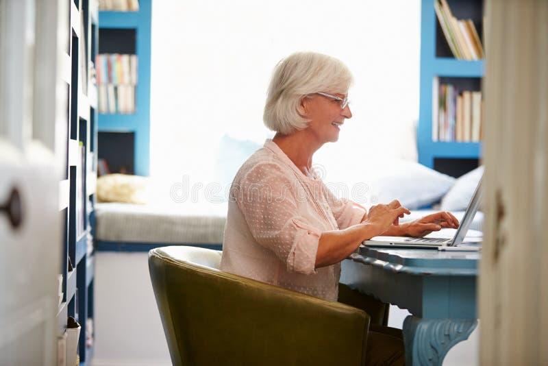 Hogere Vrouw bij Bureau die in Huisbureau werken met Laptop stock foto
